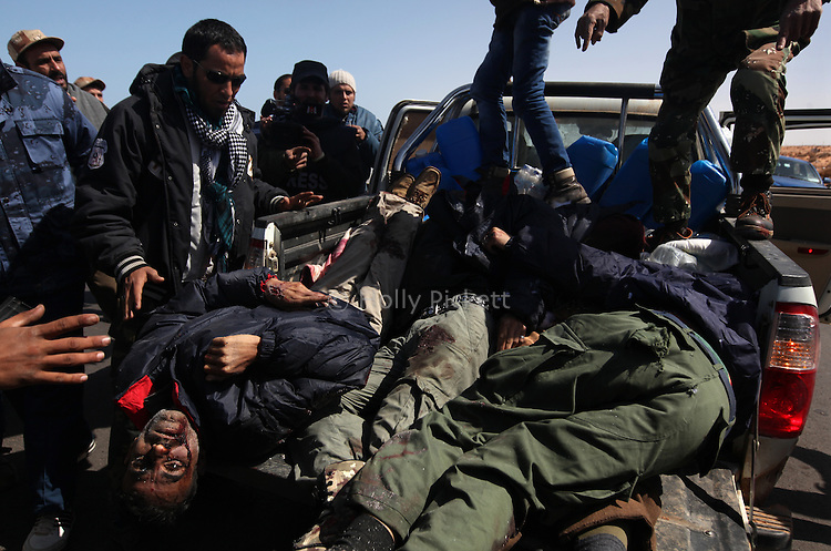 Opposition rebels view the bodies of four dead fighters near a large oil refinery in Ras Lanuf, Libya, March, 11, 2011. Loyalist forces of Col. Muammar Qaddafi pushed rebels back from the strategic oil town with air strikes, artillery and small arms fire.