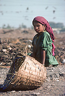 A young girl employed to collects used charcoal scraps for recycling in India. Child labor as seen around the world between 1979 and 1980 - Photographer Jean Pierre Laffont, touched by the suffering of child workers, chronicled their plight in 12 countries over the course of one year.  Laffont was awarded The World Press Award and Madeline Ross Award among many others for his work.