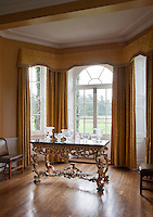 Gold damask drapes frame the windows of the dining room which look out onto the grounds
