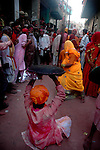 A lady bits up a man with a long stick while he uses a pad to protect himself from it. The festival of lathmar holi starts with men taunting women with songs having sexual connotation agasinst which the ladies hit them hard with long sticks. the man uses padding to stop getting hurt  . As holi itself is played among men and women but only in Barsana holi is still celebrated in the way its written in the epics. Barsana, Uttarpradesh, India