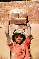 January 1979, New Delhi, Delhi, North-Central India, India --- In India, this little girl struggles under the weight while carrying a heavy load of bricks on her head. She is employed at a brick-making plant in New Delhi. --- Image by © JP Laffont
