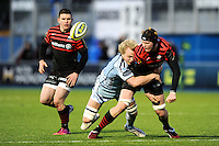 20130127 Copyright onEdition 2013©.Free for editorial use image, please credit: onEdition..Tom Jubb of Saracens passes as he is tackled by Luke Hamilton of Cardiff Blues during the LV= Cup match between Saracens and Cardiff Blues at Allianz Park on Sunday 27th January 2013 (Photo by Rob Munro)..For press contacts contact: Sam Feasey at brandRapport on M: +44 (0)7717 757114 E: SFeasey@brand-rapport.com..If you require a higher resolution image or you have any other onEdition photographic enquiries, please contact onEdition on 0845 900 2 900 or email info@onEdition.com.This image is copyright onEdition 2013©..This image has been supplied by onEdition and must be credited onEdition. The author is asserting his full Moral rights in relation to the publication of this image. Rights for onward transmission of any image or file is not granted or implied. Changing or deleting Copyright information is illegal as specified in the Copyright, Design and Patents Act 1988. If you are in any way unsure of your right to publish this image please contact onEdition on 0845 900 2 900 or email info@onEdition.com