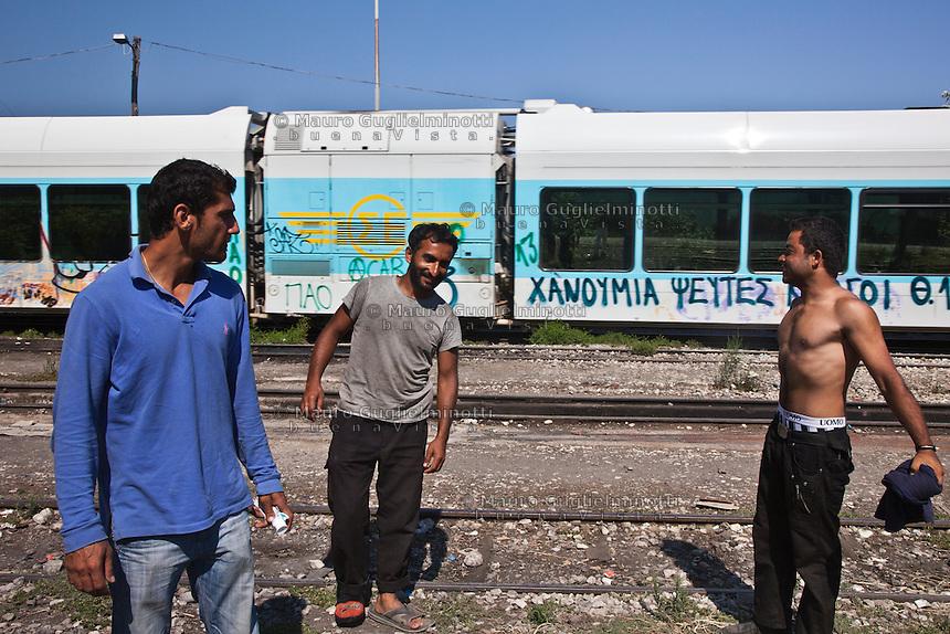 Grecia, Patrasso 2011: rifugiati afghani in un improvvisato campo in una stazione ferroviaria abbandonata. Tre uomini lungo i binari. Dietro un vecchio treno dismesso. Grece ville de Patras  2011 - refugies afghans dans une gare abandonnee