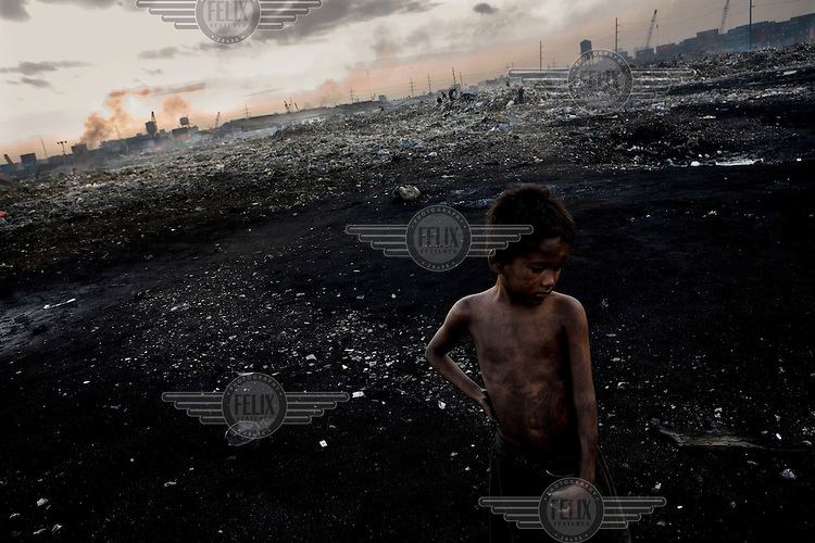 A homeless boy covered in dirt at the city's toxic rubbish dump. The dump provides food and shelter for many homeless people. .