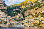 The late afternoon sun illuminates the famous town of Positano on the Amalfi Coast in Italy.