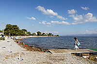 Pictured: A woman walks on the beach in the Markopoulos area, near Oropos, which is covered by debris washed ashore, from the floods on the island of Evia, across the Evia strait washed ashore. Monday 10 August 2020<br /> Re: Aftermath of flooding caused by thunderstorms and torrential rains on the island of Evia, Greece<br /> Victims included an eight-month-old baby and two people in their 80s. Rescuers found their bodies in houses in the village of Politika.<br /> Search efforts are continuing for two other people reported missing.<br /> The flooding has blocked roads and damaged houses on the island, north-east of Athens.<br /> According to officials, the baby died after floodwaters submerged a ground-floor flat. The parents were unharmed.