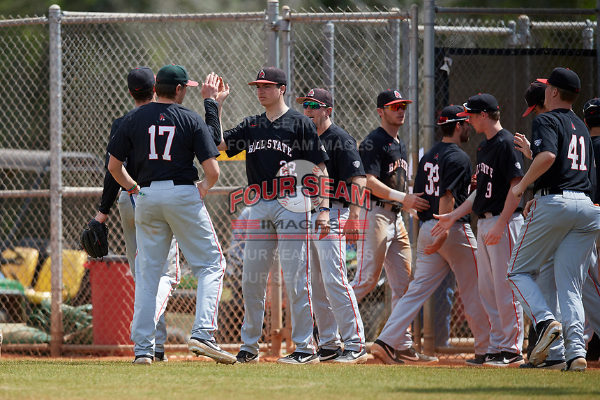 Ball State Cardinals Chayce McDermott (22) high fives teammates during a game against the Saint Joseph's Hawks on March 9, 2019 at North Charlotte Regional Park in Port Charlotte, Florida.  Ball State defeated Saint Joseph's 7-5.  (Mike Janes/Four Seam Images)