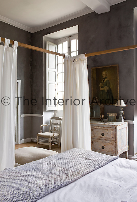 An 18th century provencale commode is placed between the windows in this four-poster bedroom