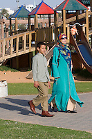 Tripoli, Libya, North Africa - Modern Libyan Woman's and Young Boy's Clothing Styles as seen in Public Park near the Green Square, downtown Tripoli.