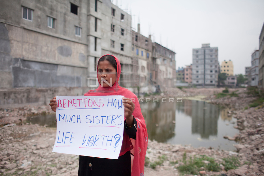 A garment worker shows protest banner in front of the Rana Plaza site during a protest rally in front of the collapse site in Savar, near Dhaka, Bangladesh. Almost every week, the activists from different NGOs stage the protest against the delay of the compensation payment.