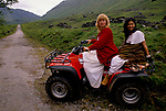 'CLAN, THE' SCOTLAND, A GROUP WHO SPEND THEIR WEEKENDS AT A CAMP IN GLEN CROE RECREATING THE LIFE OF A SCOTTISH CLAN BEFORE THE DEFEAT OF BONNIE PRINCE CHARLIE BY THE ENGLISH AT THE BATTLE OF CULLODEN IN 1746. DIANE DAVIDSON & THE CHIEF'S WIFE CARY RIDING TWO UP ON A QUAD BIKE. CARY WAS FIRST ATTRACTED BY THE CLAN'S CLOTHES & LATER THEIR PHILOSOPHY., 1989