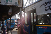 Commuter climb on a bus at the bus station outside Howrah Station in Howrah, Kolkata, West Bengal  on Friday, May 26, 2017. Photographer: Sanjit Das