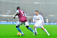 Pictured: Friday 26 December 2014<br /> Re: Premier League, Swansea City FC v Aston Villa at the Liberty Stadium, Swansea, south Wales, UK.<br /> <br /> Swansea's Gylfi Sigurddson watching the footwork of Jores Okore