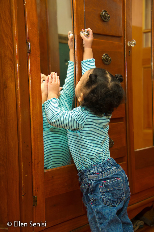 MR / Schenectady, NY. Toddler (1 year and 2 months old, African-American and Caucasian) reaches up to grasp door handle on furniture. MR: Dal4. ID: AM-HD. © Ellen B. Senisi