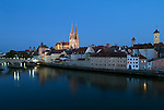 Germany, Bavaria, Upper Palatinate, Regensburg at river Danube: Old Town with Stone Bridge, City Gate, Cathedral St. Peter and Clock Tower of the Old Cityhall at dusk