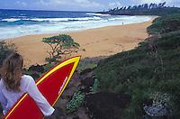 Woman walking down to beach with red surfboard, Kealia, east side of Kauai, Hawaii