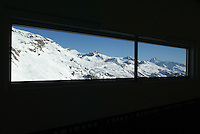 Switzerland. Valais. Crans Montana. Winter ski resort. View on Aminona and the swiss alps through a window at the Cry d'Er station. © 2005 Didier Ruef