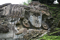 Pictured:  Images of the rock carvings of hindu god, godess in the hills of Unokoti, Agartala, Tripura.Unakoti hill, literally meaning one less a koti in Bengali, hosts an ancient Shaivite place of worship with huge rock reliefs celebrating Shiva. <br /> It is the prime tourist spot of Unakoti District Tripura in the Kailashahar Subdivision in the North-eastern Indian state of Tripura. It is Shiva pilgrimage and dates back to 7th – 9th centuries if not earlier. <br /> Unakoti is a historic Shaiva pilgrimage spot and dates back to 7th – 9th centuries if not earlier. While the marvellous rock carvings, murals with their primitive beauty form the chief attraction, natural beauty including mountain scenery and waterfalls are an added bonus. As per Hindu theological traditions, when Lord Shiva was going to Kashi along with one crore gods and goddesses including him, he made a night halt at this location. He asked all the gods and goddesses to wake up before sun rise and proceed for Kashi. It is said that in the morning, except Shiva himself, no one else could get up so set out for Kashi himself cursing the others to become stone images. As a result, we have one less than a crore stone images and carvings at Unakoti. These carvings are located at a beautifully landscaped forest area with green vegetation all around which add to the beauty of the carvings.pix by-Abhisek Saha