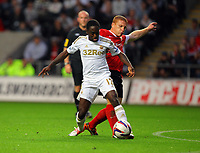 Pictured L-R: Nathan Dyer of Swansea challenged by Bobby Hassell of Barnsley. Tuesday 28 August 2012<br /> Re: Capital One Cup game, Swansea City FC v Barnsley at the Liberty Stadium, south Wales.