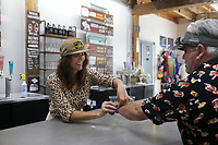 Jessy McCormick, director of hospitality, puts an entertainment district wristband on Clayton Morgan of Rogers, Friday, July 23, 2021 at Ozark Beer Company in Rogers. They expanded their patio area and added to their capacity. The brewery is in downtown Rogers and was the second largest beer producer in the state in 2019. Check out nwaonline.com/210724Daily/ for today's photo gallery. <br /> (NWA Democrat-Gazette/Charlie Kaijo)