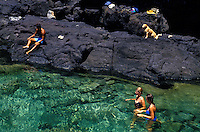 People and a dog enjoying a tide pool located along the coastal hike to Makapuu Point, east Oahu