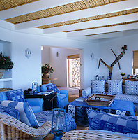 The cosy and comfortable living room is furnished with a variety of seating upholstered in blue and white fabric