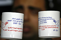 """A Palestinian shopper displays souvenir mugs for the Middle East peace conference at his shop in Gaza November 25, 2007. The United States will host a peace conference in Annapolis, Maryland next week aimed at relaunching talks on Palestinian statehood after a seven-year break. The mugs read: """"Note: Please keep this souvenir, but in case of the conference's failure; you are only asked to break this mug!!!"""". """"photo  by Fady Adwan"""""""