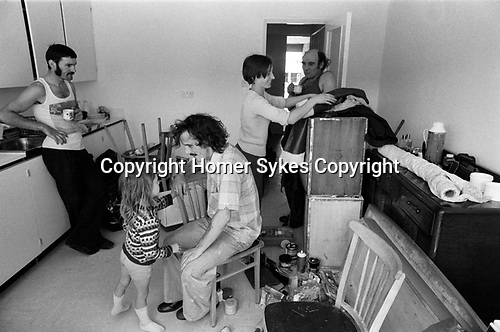 Moving into a new house, removal men having a cup of tea in the kitchen before leaving. Family surrounded by their furniture, wife mother, father and daughter. 1977 new home on a new housing estate  Milton Keynes Buckinghamshire 1970s UK