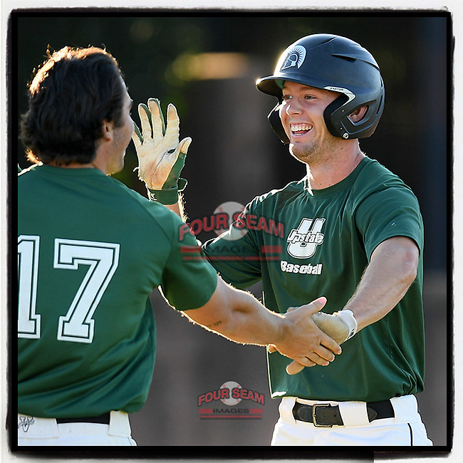 Jeff Taylor (19) of the University of South Carolina Upstate Spartans Green Team is greeted by teammates after scoring a run in the Green and Black Fall World Series Game 1 on Friday, October 30, 2020, at Cleveland S. Harley Park in Spartanburg, South Carolina. It was not enough, as Black won, 2-1. (Tom Priddy/Four Seam Images)