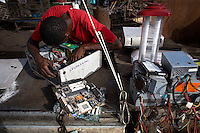 A man examines a hard drive at Agbogbloshie dump, which has become a dumping ground for computers and electronic waste from all over the developed world. Hundreds of tons of e-waste end up here every month. It is broken apart, and those components that can be sold on, are salvaged.