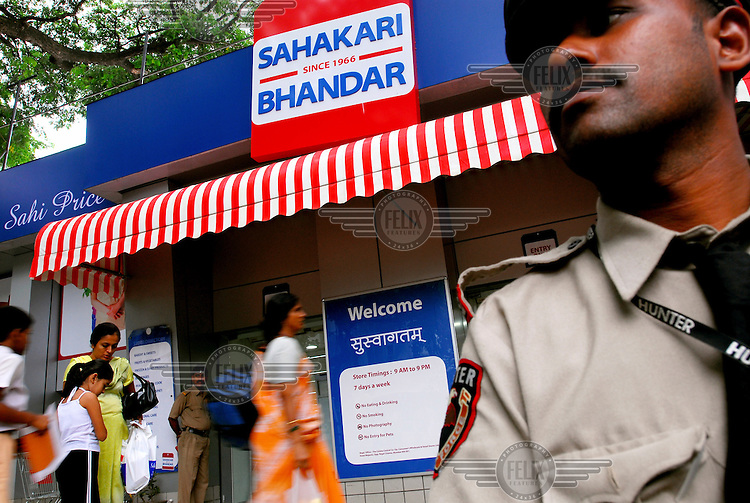 Security guards watch over shoppers leaving the Matunga branch of the Sahakari Bhandar supermarket chain. The formerly state-managed department store has been recently renovated by Reliance Industries Limited (RIL), India's largest private sector company.