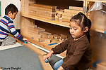 Preschool 3-4 year olds boy and girl playing separately with trains and wooden track