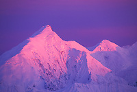 Pink alpenglow on the snow covered mount Brooks (left) of the Alaska Range mountains. Denali National Park, Alaska.