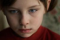moody melancholy girl (8-9) looks past camera
