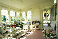 Welcoming sun porch with wicker furniture and sun streaming from windows