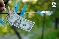 Man's hand taking one US dollars banknote hanging on clothesline (Licence this image exclusively with Getty: http://www.gettyimages.com/detail/sb10065474af-001 )