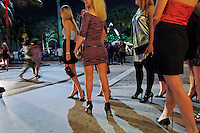 Lincoln Road night life--a bachelorette party waits for the third cab for all the girls to celebrate a dinner and dancing. Shoppers walk along Lincoln looking at colorful window fronts.