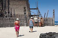 Tour guide wearing traditional Hawaiian leaf cape next to visitors in Pu'uhonua o Honaunau National Historical Park, Big Island.