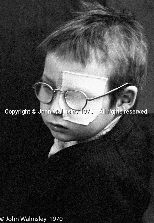Boy wearing NHS spectacles also has a large eye patch to help correct a deficiency in the other eye, Vittoria Primary School, Islington, London.  1970.