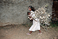 Eritrea. Southern Debud Zone. Maiado. Small village in the country. Mother carries her daughter in her arms and wood on her back. The wood was cut in the forest and will be burned  cooking food in the kitchen.  © 2002 Didier Ruef