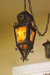 Albany California<br />Even more ornate is this tapered four-sided pendant swag, whose ultra-delicate filigree is extended into a decorative cage above and below.  The translucent amber art glass in this fixture is also common to many Craftsman-era lighting fixtures.