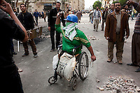 A man in a wheel chair and anti government protesters on Tahrir square. Throughout Friday, 4 February, anti government protesters protected their positions from pro Mubarak supporters around Tahrir square, the scene of heavy clashes between pro and anti government protesters. Continued anti-government protests take place in Cairo calling for President Mubarak to stand down. After dissolving the government and allowing for talks with opposition parties Mubarak still refuses to step down from power...