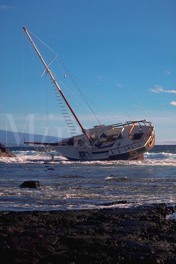 Storm-damaged sailboat beached on a rocky coast.