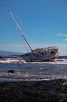 Storm-damaged sailboat beached on a rocky coast.