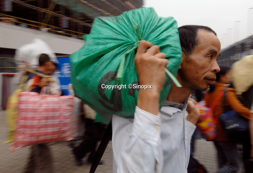 Migrant workers and job seekers arrive at Guangzhou Railways station at the beginning of the Chinese New Year carrying their bags and belongings. Millions of workers pass through this station mostly on the way to factory  production and construction projects in Guangdong Province, China..17 Mar 2007.