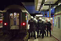 Switzerland. Canton Ticino. Lugano. Railway station. A group of police officers from TPO (Transport Police). The policemen wear the special riot police black uniforms and helmets. They are standing on the platform and control the FC Luzern football club's supporters before they leave in a chartered train. A protective metal fence is used during sport events. TPO (Transport Police) is the Swiss Federal Railways Police. Swiss Federal Railways (German: Schweizerische Bundesbahnen (SBB), French: Chemins de fer fédéraux suisses (CFF), Italian: Ferrovie federali svizzere (FFS)) is the national railway company of Switzerland. It is usually referred to by the initials of its German, French and Italian names, as SBB CFF FFS. 2.06.2017 © 2017 Didier Ruef