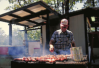 Man BBQing on outdoor grill. Ed of Ed's Country Store. Texas, Texas Hill Country.