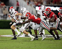 ATHENS, GA - SEPTEMBER 18: Luke Doty #4 is tackled from behind by Channing Tindall #41 during a game between South Carolina Gamecocks and Georgia Bulldogs at Sanford Stadium on September 18, 2021 in Athens, Georgia.