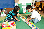 Education preschool 3-4 year olds boy and girl working together on floor puzzle