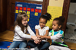Education Preschool group of three girls placing hands on top of each other, playing game